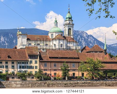 Solothurn, Switzerland - 19 July, 2013: buildings along Aare river with the towers of the St. Ursus cathedral in the background. The St. Ursus Cathedral is a Swiss heritage site of national significance.