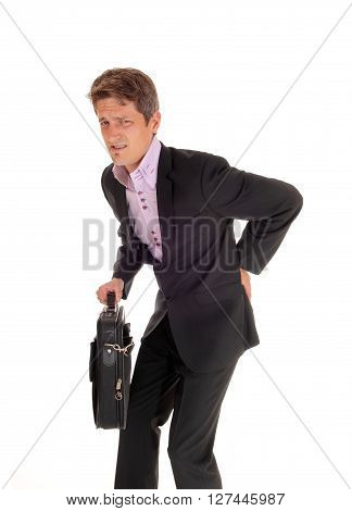 A young business man walking in a suit holding his back for arthritis pain isolated for white background.