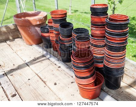 Stacks of dirty plastic flowerpots on a wooden bench in a sunny greenhouse