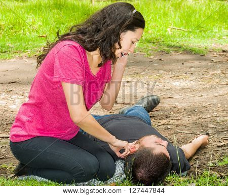 Young man lying down with medical emergency, woman sitting by his side calling for help and checking pulse, outdoors environment.