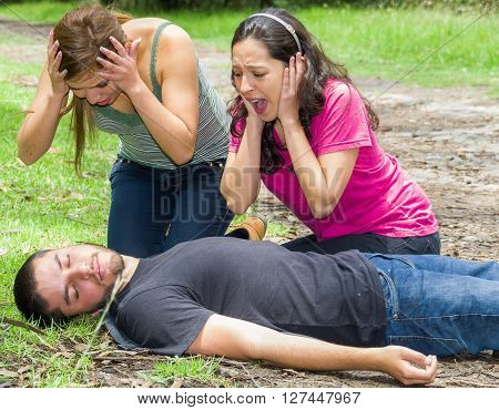 Young man lying down with medical emergency, two young women acting hysterically, outdoors environment.