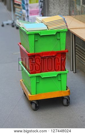 Moving Books in Plastic Crates With Cart at Street