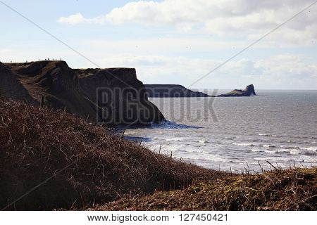 Worm's Head as seen from Rhossili Bay, Rhossili, on the west Gower Peninsular, West Glamorgan, Wales, UK, a popular Welsh coastline attraction for tourist visitors of outstanding beauty