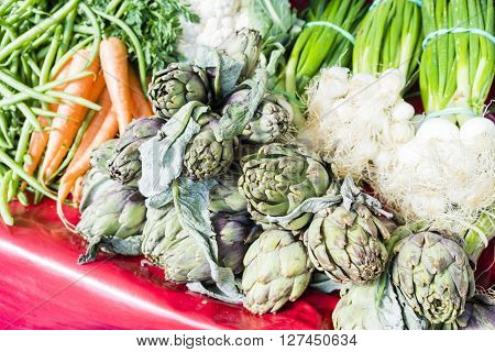 Artichokes, scallions, carrots and beans in a market in Paris, France