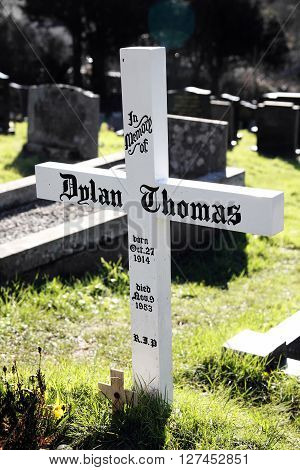 Laugharne,Wales, UK, February 24, 2016 : The grave of Dylan Thomas is marked by just a simple plain tombstone white cross in St Martin's Church overspill cemeter