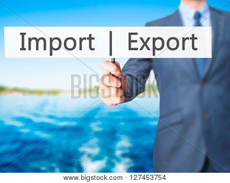 Import  Export - Businessman Hand Holding Sign