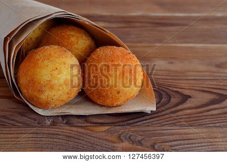 Arancini rice balls. Fried rice balls in paper on brown wooden background. Snack, street food