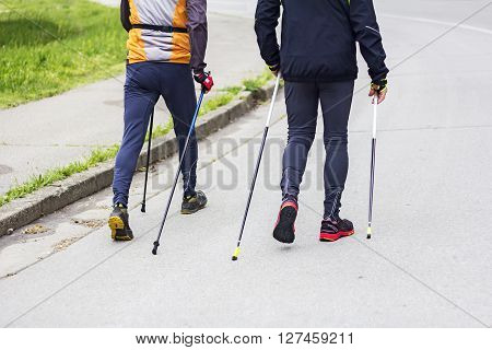 Two men nordic walking race on city street