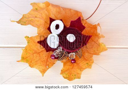 Beautiful brooch flowers made from felt, beads and metal leaves, fallen yellow leaves on a white wooden background