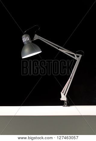 Single adjustable hinged desk lamp attached to white surface over black background