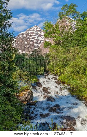 the maroon bells and waterfall in summer