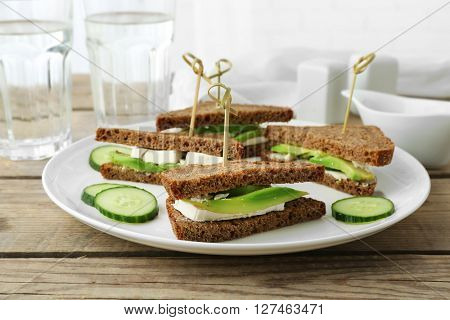 Vegetarian avocado sandwich with dark rye bread on a white plate