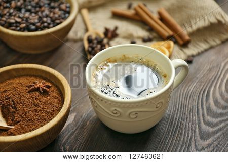 Coffee with beans and spices on wooden table closeup
