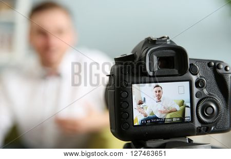 Young male blogger recording video at home