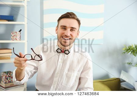 Young male blogger holding glasses in living room, close up