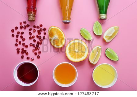 Different fruit drinks with fresh fruits on pink background