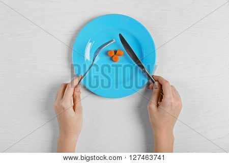 Female hands holding fork and knife on a plate with slices of baby carrots on white table.