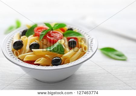 Cooked penne pasta with olives, fresh tomatoes and basil in white plate on wooden table