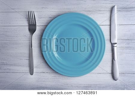 Empty plate with silver cutlery on wooden background