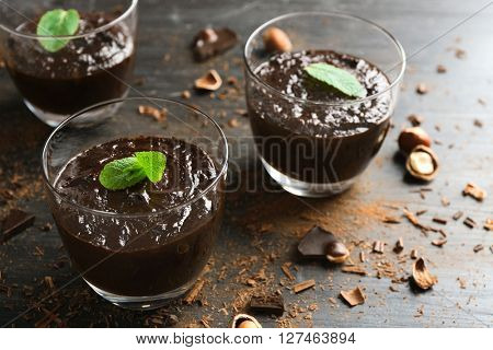 Glass cups of chocolate dessert with fresh mint and hazelnuts on black wooden table