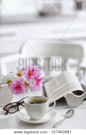 White cup of the coffee and fresh flowers on wooden table in a light room..