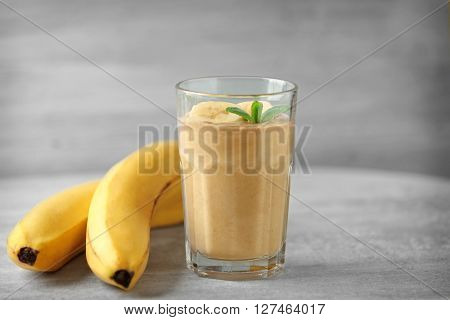 Glass of fresh banana cocktail on wooden table
