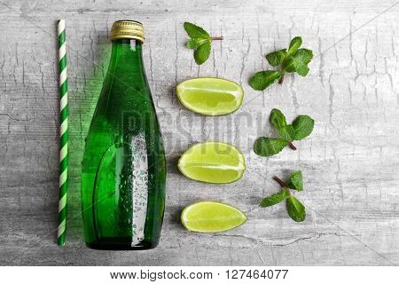 Fresh cocktail preparation: soda bottle, slices of lime and straw on grey table background, top view