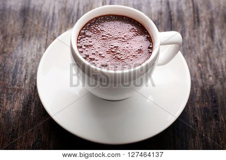Cup of hot coffee on rustic wooden background