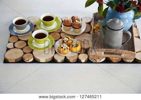 Table setting with tea and cakes on wooden background