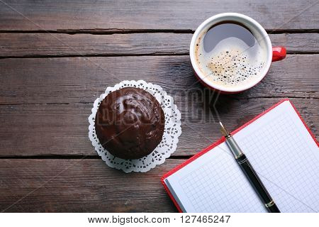 Cup of coffee with chocolate cake and open blank notebook on wooden background