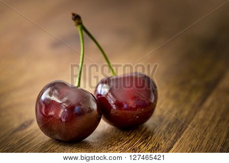 two red cherries fruit on wooden table