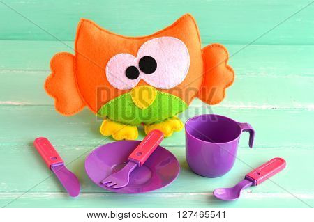 Funny felt owl toy, children's tableware on green wooden background. Children's game