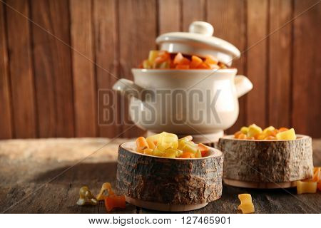 Raw pasta in pan on wooden background