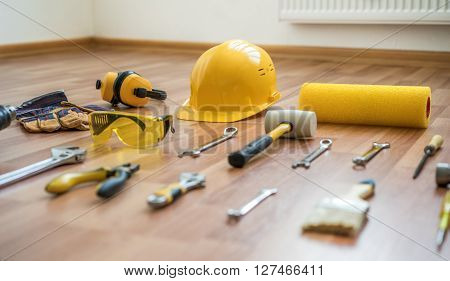 helmet with construction tools on a background of a new laminate