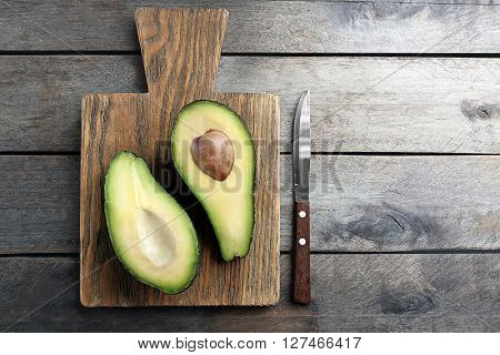 Sliced avocado with knife on wooden cutting board