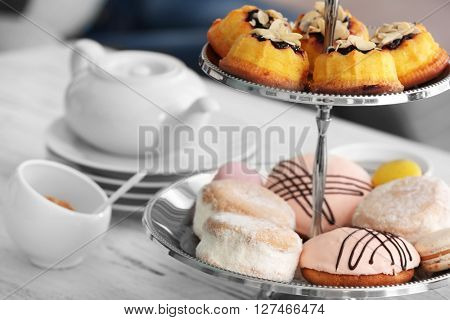 Cake stand with different sweets and tea