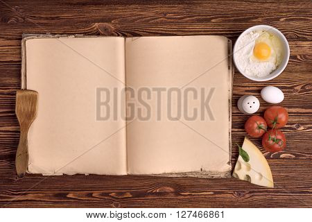 old cook book, the ingredients for a meal on a background of vintage wood