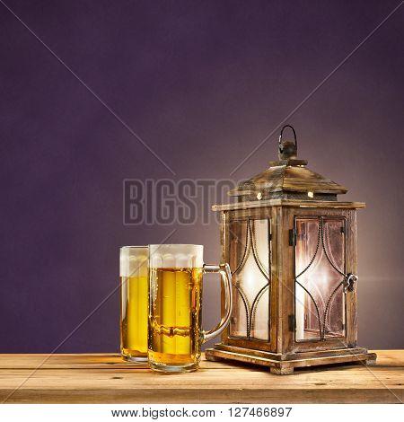 old lantern with beer on purple vintage background