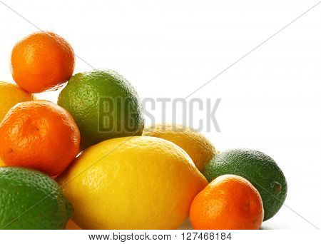 A heap of mixed citrus fruit including   lemons, tangerines, limes isolated on a white background, close up