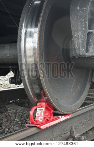 Rusty and polished freight train wheel on railroad track. Train shoe propped wheel train.