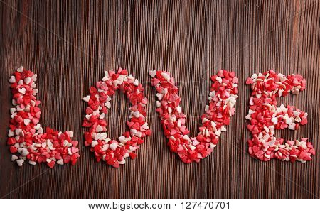 Love word with candies on wooden background