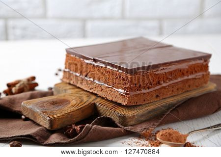 Delicious chocolate cake on wooden cutting board closeup