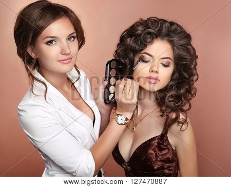 Curly Hair. Beauty Makeup. Professional Artist Woman Applying Make Up Sensual Brunette Girl Model Wi