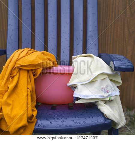 Various laundry in a pink washbowl standing on the plastic chair outdoor cropped shot