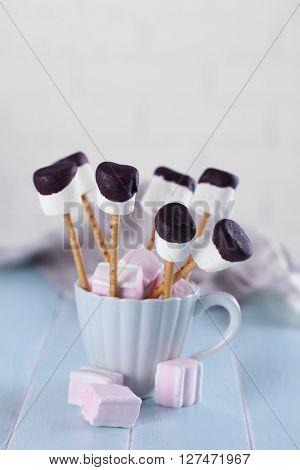 Tasty marshmallows with chocolate on sticks, close up