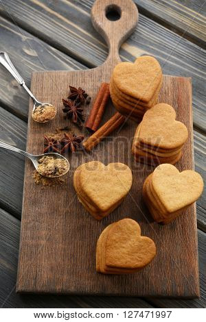 Heart shaped biscuits and cinnamon on cutting board