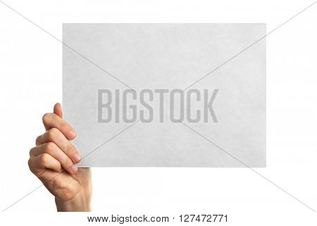 Male hand holding clean sheet of paper, isolated on white