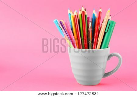 Colorful stationery in cup on pink background