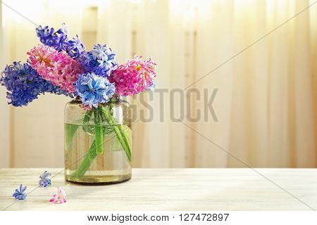 Hyacinth flowers on table in front of curtain background