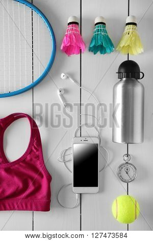 Sport equipment and clothes with mobile phone on white wooden background